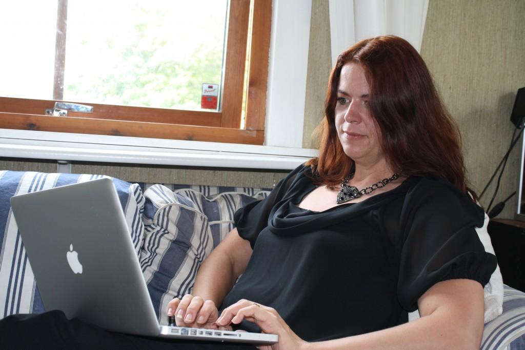 Åsa S skriver i soffan bredd